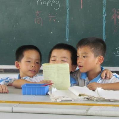 Een Projects Abroad vrijwilliger werkt met kinderen in China en luistert naar kinderen die hun leesvaardigheid oefenen voor de klas.